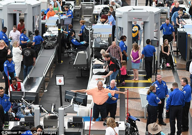 man being searched at tsa checkpoint in busy airport