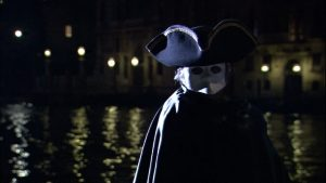 man in mask at Venice carnival at night on the grand canal