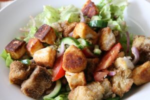 panzanella is a tuscan salad made with bread, tomatoes, garlic and olive oil